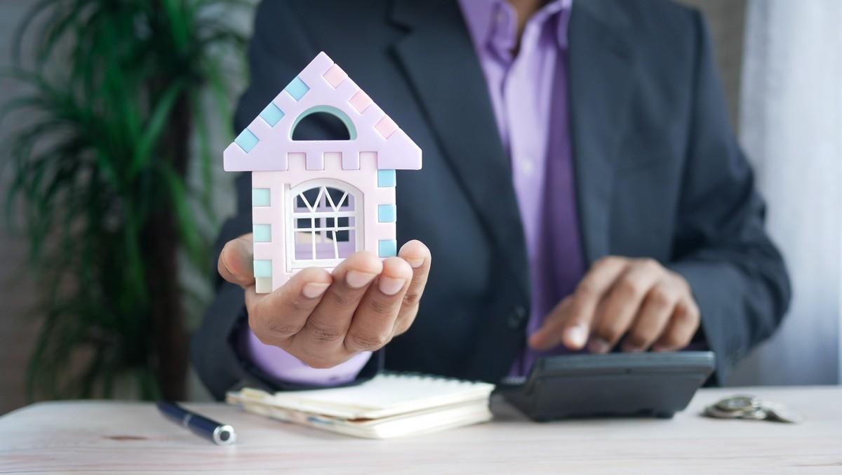 Muž drží domeček symbolizující výhodné stavební spoření na bydlení.