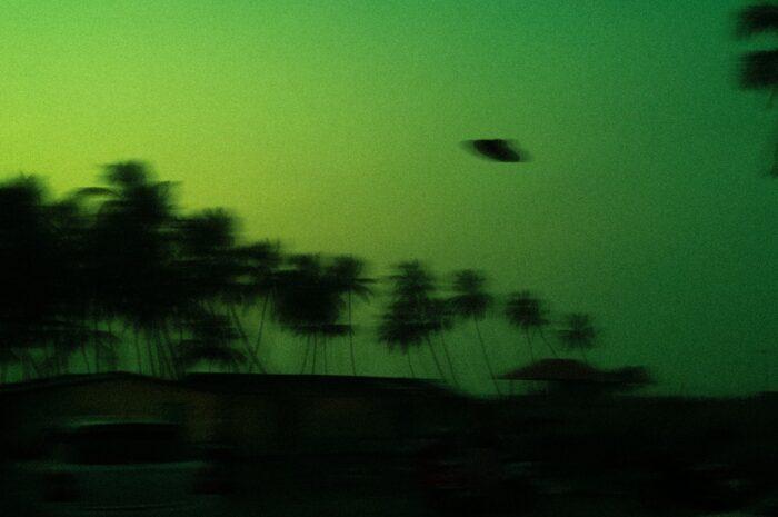 UFO vznášející se nad krajinou na rozmazaném snímku.